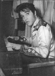 Elvis Presley playing piano in black and white picture