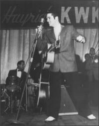 Elvis Presley singing with a cut smile
