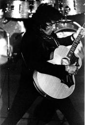 Elvis Presley wearing black outfit and playing guitar