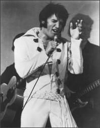 Elvis Presley wearing white outfit and singing passionately